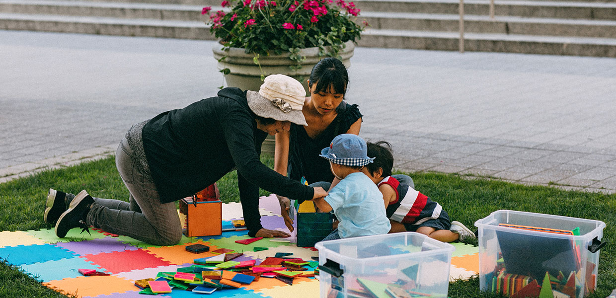 Family enjoying art projects on lawn in Kendall Square